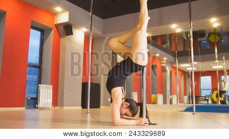 Attractive Plastic Woman Performing Pole Dance Elements On A Pole, Close Up