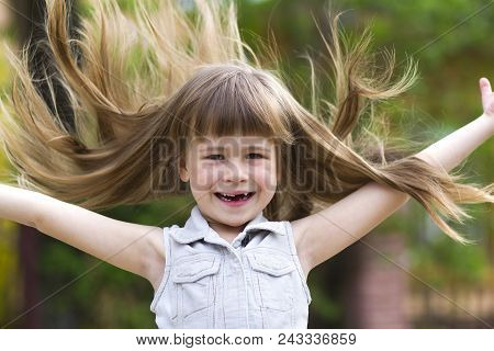 Pretty little preschool girl in sleeveless white dress with beautiful long blond hair blown by wind, funny toothless smile and spread arms on blurred background. Innocent happy childhood concept. poster