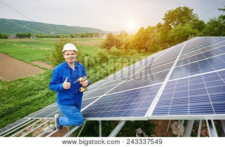Construction worker with screwdriver looking in camera with thumb-up gesture on photo voltaic panel solar system shiny surface and lit by sun green fields background. Alternative energy concept. poster