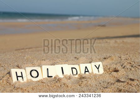 Letters Of Holiday On A Sunny Beach With Sea In Background.