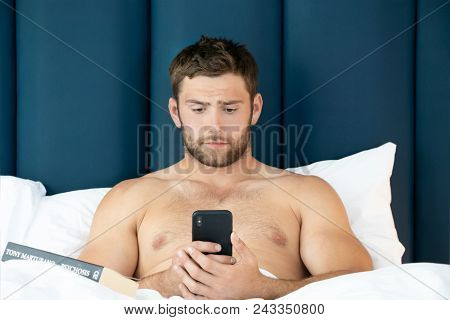 Handsome Man With Abs, Muscular, Hunky Body And Beard Lies Naked In Between White Sheets On Bed Usin
