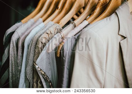 Collection Of Fashion Clothes In Beige Colors, Designer Dresses Hanging On The Rack Close-up