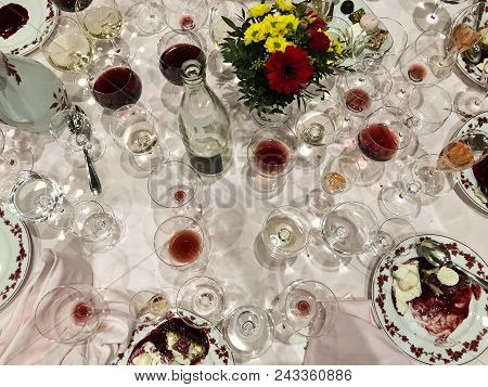 After A Long And Elegant Dinner, A Table With White Tablecloth Is Full Of Empty And Half-empty Wine