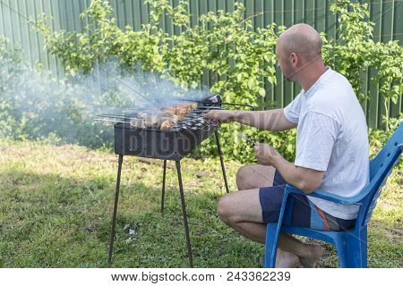 Man Cooking Meat On Barbecue. Young Couple Making Barbecue In Their Garden. Man Cooking Meat On Barb
