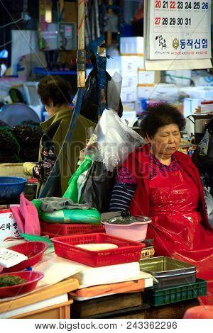 SEOUL-SOUTH KOREA, MAY 18, 2018:  Woman sleeping at her stand at the fish market in south Korea.  Noryangjin Fish Market is an extensive farmers fish market in the neighborhood of Noryangjin-dong