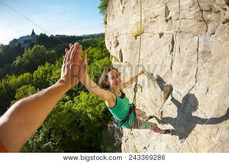 The Girl Climbs The Rock On The Background Of A Forest Landscape. Fitness In Nature. The Woman Gives