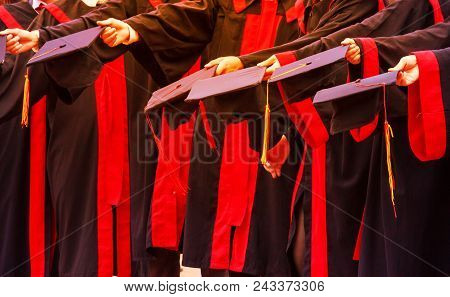 Graduate Students Hold Hats In Hands In University Graduation Success Ceremony. Congratulation On Ed
