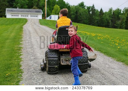 Children On The Farm. Older Brother Driving A Lawn Mower, Younger Brother Running After Him
