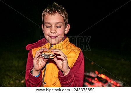 Boy Eating Smores By The Campfire. Smiling Child Enjoys Dessert At A Summer Camp