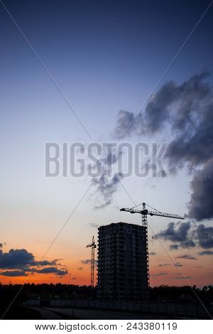 Crane And Construction Site Against Sunset. Unfinished Building Construction And Building Cranes Aga