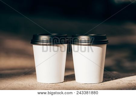 Two Cups Of Coffee To Go In White Paper Cups In Sunlight. Place For Text. Cofffee Mood Concept.