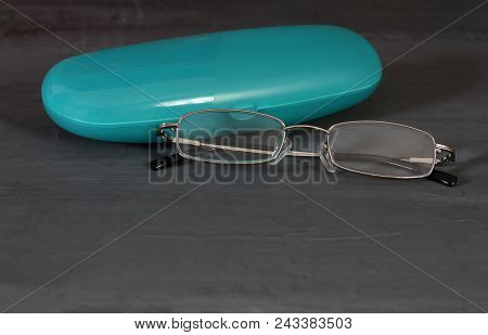 Spectacle-case With Glasses Over Dark Background. Turquoise Case
