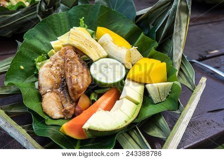 Healthy Lunch Of Fish And A Salad Of Fresh Fruit And Vegetables On A Biodegradable Leaf Plate: Banan