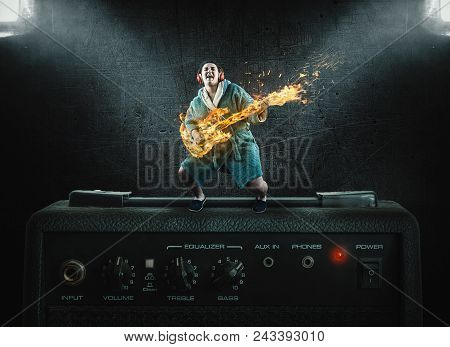 Woman In Dressing Gown Is Playing On Flame Guitar Standing On Amplifier.