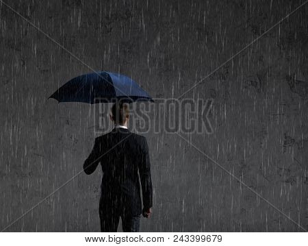 Businessman With Umbrella Standing Under The Rain. Dark, Dramatic Background. Business, Failure, Cri