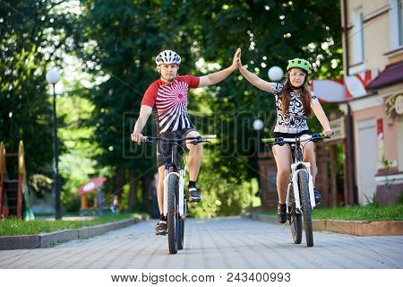 Cyclist Couple In Cycling Clothing And Helmets Giving High Fives Riding Bikes Down Paved Street In P