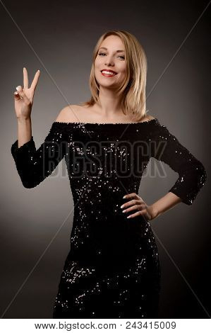 Young Beautiful Woman Shows V A Sign Of Victory. An Attractive Girl In A Dress Shows A Figure Of Two