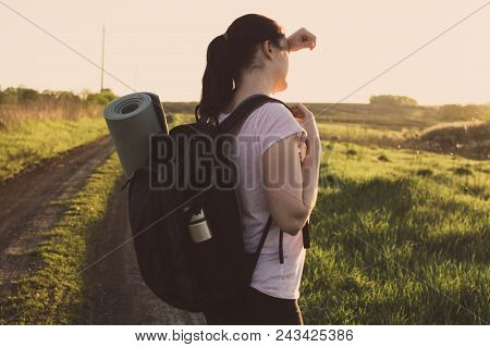 Lonely Female Backpacker With Tourist Mat Standing On The Empty Endless Road And Looking At The Hori