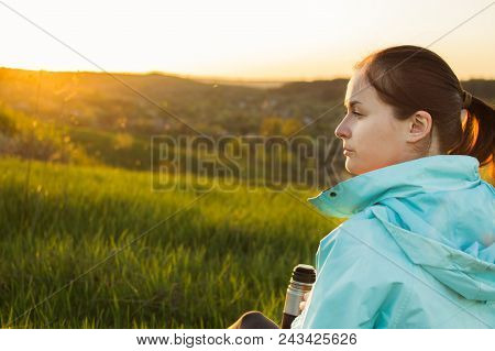 Young Female Traveller Is Drinking A Coffee From The Travel Metallic Cup On The Sunset. Concept Of T