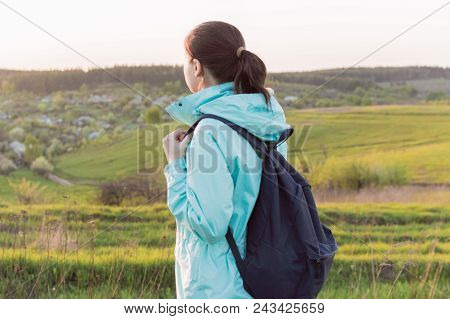Lonely Female Traveller In Blue Outerwear And With Dark Blue Backpack Standing On The Hill Covered W