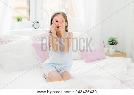 Small Pretty Female Child Holds Tasty Sweet Doughnut, Poses In Bedroom On Comfortabled Bed, Dressed