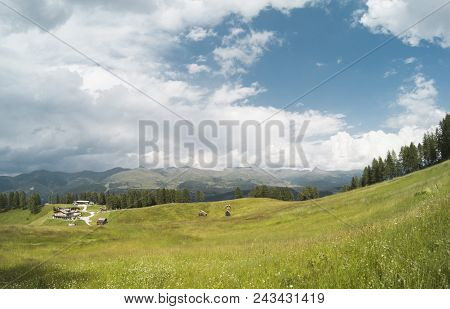 Beautiful View On Landscape Of Alps Moutains And A Gree Forest With A With Small Houses In The Valle