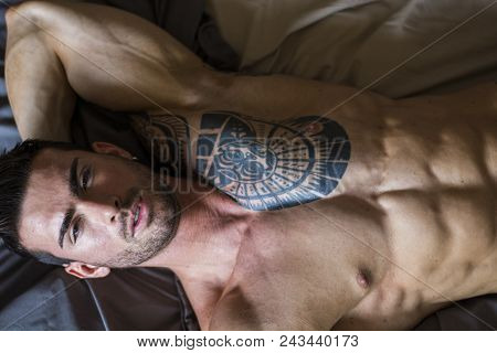 Shirtless Muscular Sexy Male Model Lying Alone On Bed In His Bedroom, Looking Away With A Seductive
