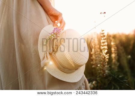 Woman Holding Straw Hat With A Ribbon On Flower Field Background. Warm Sunset Light Beams.