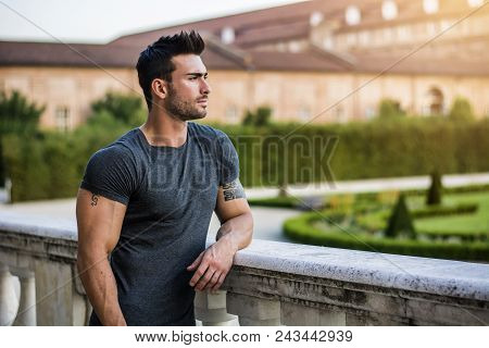 Handsome Muscular Man With Tattoo Posing In European Luxury Garden In Turin, Italy