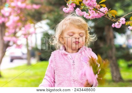 Little Charming Blond Girl Closed Her Eyes With Pleasure In The Garden With Blooming Sakura