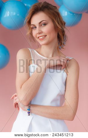 Sexy Young Girl Smiling In White Dress Portrait. Pink Background With Blue Balls