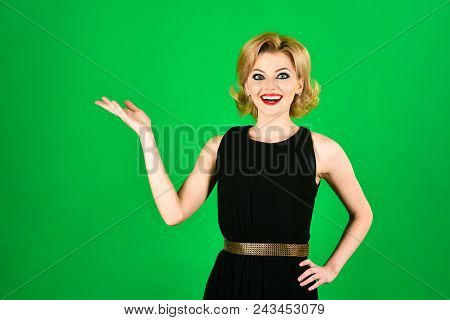 Blonde Girl With Evening Makeup Posing On Green Background. Beautiful Makeup And Black Dress. Skin A