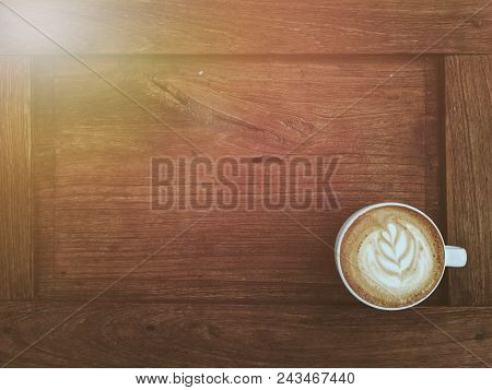 Latte Coffee In White Cup On Old Wooden Table With Light Flare At Corner Show Warm Lighting.