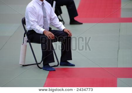 The karate referee sitting beside the mat poster