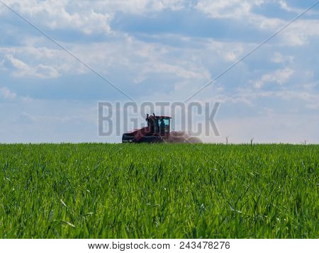Red Tractor On A Green Field Cultivating Fertile Land