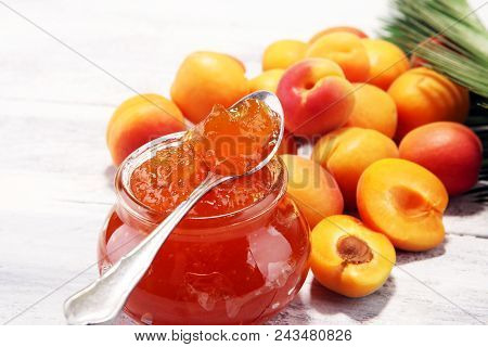 Apricot Jam And A Bunch Of Fresh Apricots On Wooden Table.