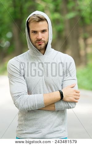 Athlete with bristle with fitness tracker or pedometer. Sportsman training with pedometer gadget. Fitness tracker concept. Man athlete on pensive face with sport fitness gadget, nature background. poster