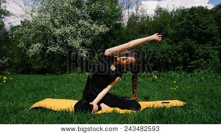 Beautiful Young Girl Doing Warm-up On A Rug For Yoga In A Park In Summer, Slow Motion. A Woman With