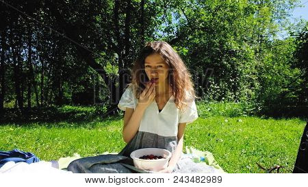 European Girl Eats Strawberries In The Nature. A Young Woman Sits On The Grass And Eats Berries On A