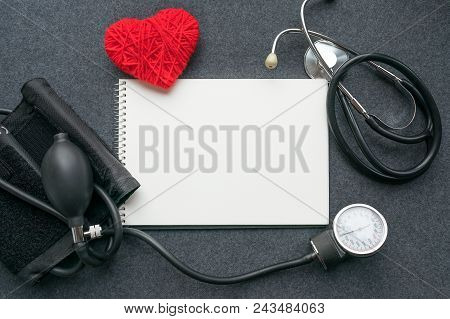 Medical Mockup Flat Lay. White Notebook, Red Thread Heart With Tonometer On Grey Table. Sphygmomanom