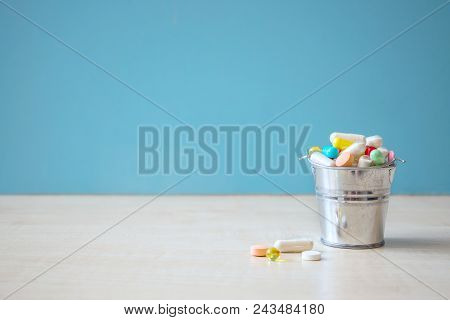 Assorted Pharmaceutical Medicine Pills, Tablets And Capsules In The Bucket Over Blue Background. Pha