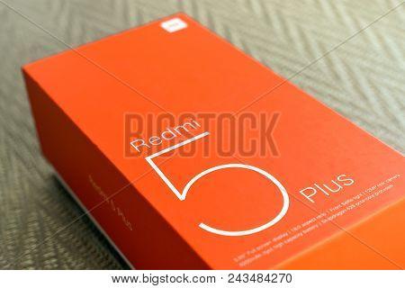 Kiev, Ukraine - May 28, 2018: Xiaomi Redmi 5 Plus Black New Smartphone With Orange Box Close Up Deve