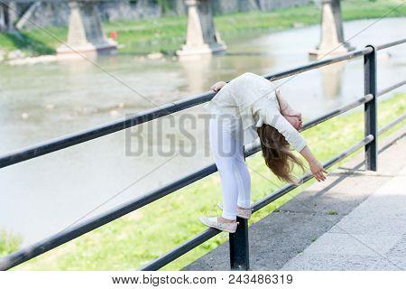 Kid girl bends backwards as flexible gymnast near railing at riverside background. Girl kid gymnast demonstrates flexibility of body. Flexibility concept. Child flexible sporty girl gymnast. poster