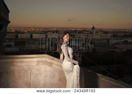 Sensual Woman. Fashion Model Style And Hairstyle. Woman In White Wedding Dress On Evening City View,
