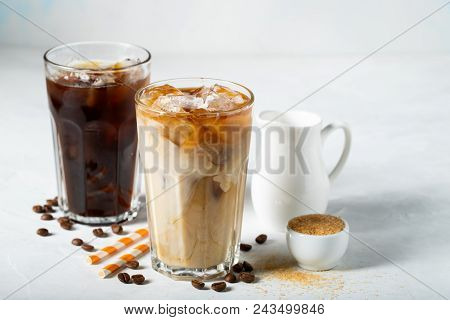 Ice Coffee In A Tall Glass With Cream Poured Over And Coffee Beans. Cold Summer Drink On A Light Blu