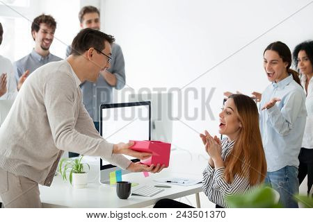 Excited Male Worker Congratulating Shocked Female Employee With Special Occasion, Presenting Gift Bo