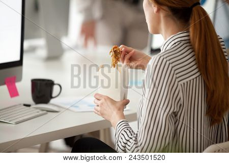 Back Close Up View Of Female Employee Eating Asian Food From Takeaway Box Using Chopsticks, Worker E