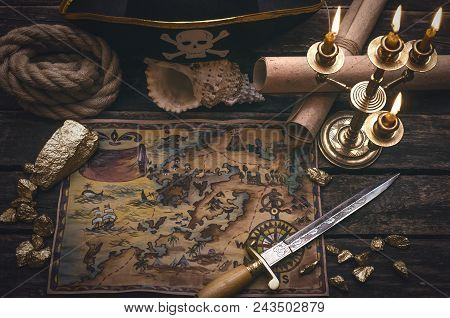 Pirate Treasure Map, Gold Nuggets, Dagger And Pirate Hat On Aged Wooden Table Background. Sea Travel