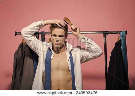 Handsome Man Face. Bachelor Brush Hair With Hairbrush In Wardrobe On Pink Background. Man With Sexy