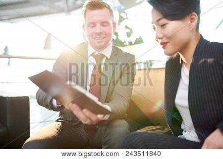 Attractive Asian Manager Listening To Her Bearded Colleague With Interest While He Sharing Creative